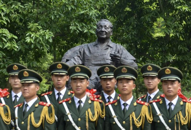 Paramilitary policemen pose for photographs in front of a statue of Deng during a ceremony to mark the upcoming 110th aAnniversary of his birth, in Guang'an
