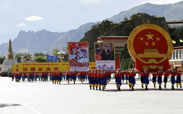 Performers carry a giant Chinese national emblem and pictures of Chinese government leaders during the celebration event at the Potala Palace marking the 50th anniversary of the founding of the Tibet Autonomous Region, in Lhasa