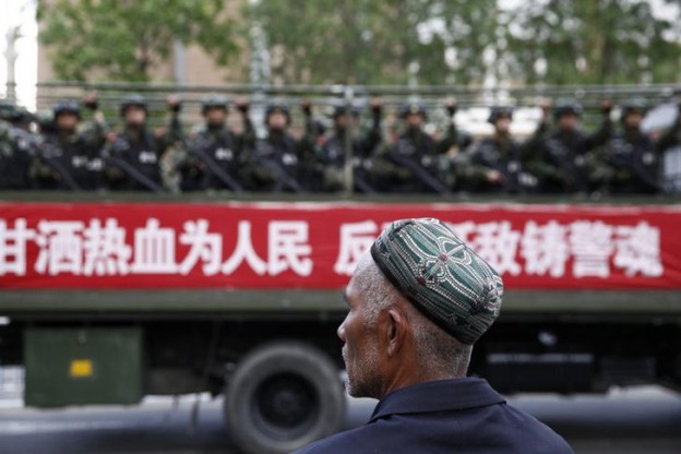 "A Uighur man looks on as a truck carrying paramilitary policemen travel along a street during an anti-terrorism oath-taking rally in Urumqi, Xinjiang Uighur Autonomous Region May 23, 2014. China launched a one-year campaign against terrorist violence in Xinjiang Uighur Autonomous Region on Friday, after 39 people were killed and 94 injured in a terrorist attack on Thursday, Xinhua News Agency reported. The Chinese characters on the banner read, ""Willingness to spill blood for the people. Countering terrorism and fighting the enemies is part of the police spirit."" Picture taken May 23, 2014. REUTERS/Stringer (CHINA - Tags: CIVIL UNREST MILITARY POLITICS) CHINA OUT. NO COMMERCIAL OR EDITORIAL SALES IN CHINA"