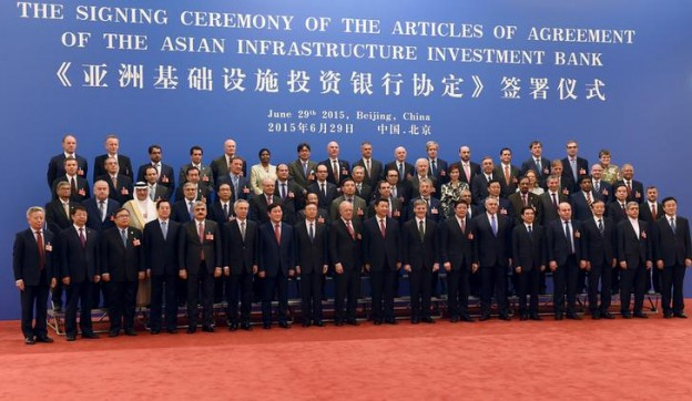 Chinese President Xi Jinping (C, front) poses for a group photo with the delegates attending the signing ceremony for the Articles of Agreement of the Asian Infrastructure Investment Bank (AIIB) at the Great Hall of the People in Beijing June 29, 2015. China will hold a 30.34 percent stake in the Asian Infrastructure Investment Bank (AIIB), the Finance Ministry said on Monday, making Beijing the largest shareholder in a bank that is expected to project the country's growing influence. REUTERS / POOL/WANG ZHAO      TPX IMAGES OF THE DAY