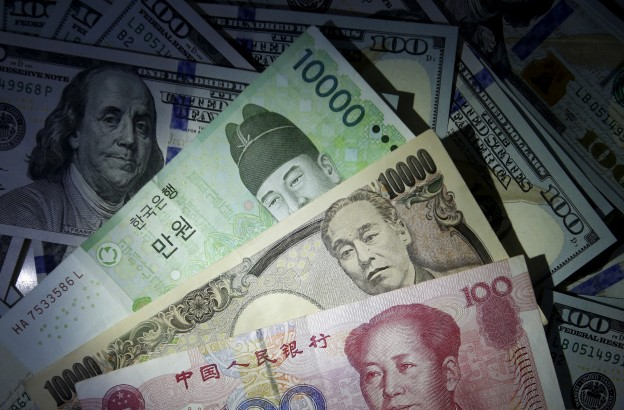 South Korean won, Chinese yuan and Japanese yen notes are seen on U.S. 100 dollar notes in this picture illustration  December 15, 2015.    REUTERS/Kim Hong-Ji//Illustration/File photo - RTX2FUK7