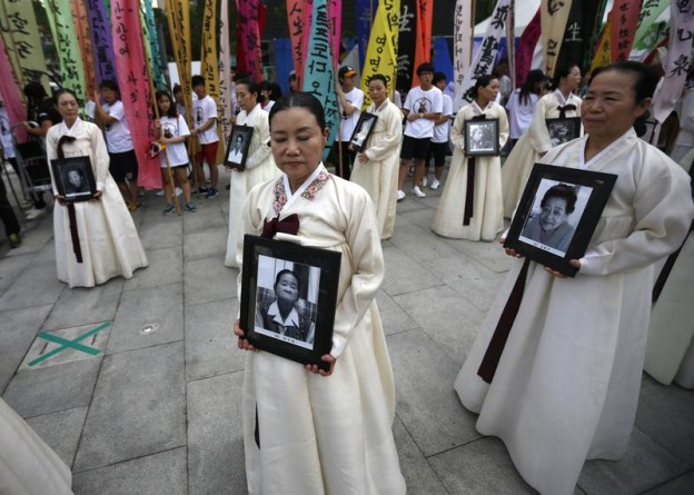 "Participants carry the portraits of Korean women who were made sex slaves by the Japanese military during World War II at a requiem ceremony for former comfort woman Lee Yong-nyeo in central Seoul August 14, 2013. Lee, who was one of the few surviving sex slaves, or ""comfort women"", for wartime Japanese soldiers, died on Sunday, according to local media. Japanese Prime Minister Shinzo Abe may make a ritual offering to Yasukuni Shrine, seen as a symbol of Japan's former militarism, on Thursday, the emotive anniversary of Japan's defeat in World War Two, media said on Wednesday. A similar move in April infuriated China and South Korea, both victims of wartime aggression. REUTERS/Kim Hong-Ji (SOUTH KOREA - Tags: POLITICS TPX IMAGES OF THE DAY CIVIL UNREST) - RTX12KU7"
