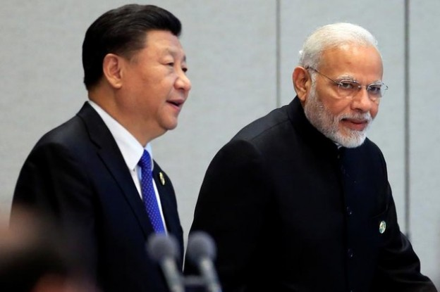 China's President Xi Jinping and India's Prime Minister Narendra Modi arrive for a signing ceremony during Shanghai Cooperation Organization (SCO) summit in Qingdao, Shandong Province, China June 10, 2018. REUTERS/Aly Song - RC1B14B27D40