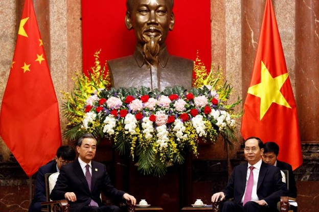 China's State Councilor and Foreign Minister Wang Yi and Vietnam's President Tran Dai Quang talk under a statue of the late Vietnamese revolutionary leader Ho Chi Minh at the Presidential Palace in Hanoi, Vietnam April 1, 2018. REUTERS/Kham - RC1F290C7D80