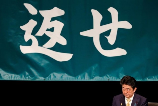 Japanese Prime Minister Shinzo Abe attends an annual Northern Territories Day rally that demands the return of a group of disputed islands controlled by Russia in Tokyo, Japan, February 7, 2019. Text on the background reads, 'return'. REUTERS/Kim Kyung-hoon - RC171AA95190