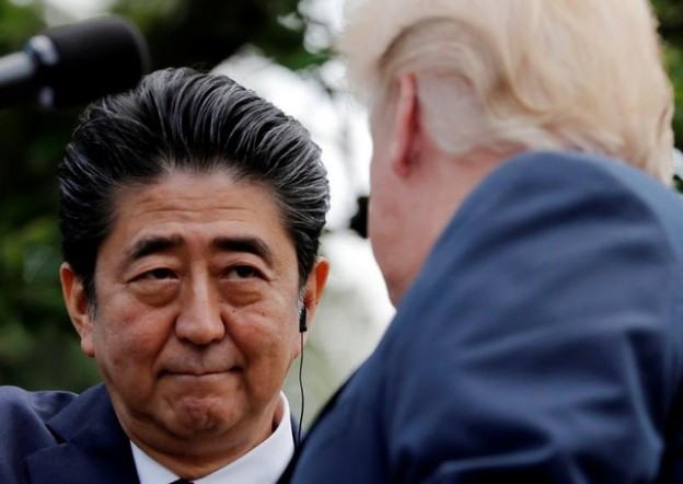 Japan's Prime Minister Shinzo Abe looks into U.S. President Donald Trump's eyes as they shake hands during a joint news conference in the Rose Garden of the White House in Washington, U.S., June 7, 2018. REUTERS/Carlos Barria - RC13DE766DC0