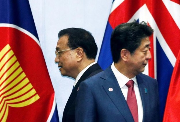 China's Premier Li Keqiang passes Japan's Prime Minister Shinzo Abe as they gather for a group photo with ASEAN leaders at the Regional Comprehensive Economic Partnership (RCEP) meeting in Singapore November 14, 2018. REUTERS/Edgar Su - RC19B87CBAD0