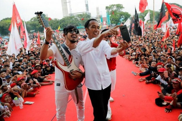 Indonesia's president and presidential candidate for the next election Joko Widodo takes selfie pictures with Indonesian band called Radja during a campaign rally in Solo, Indonesia, April 9, 2019. REUTERS/Willy Kurniawan - RC1CEC85B320