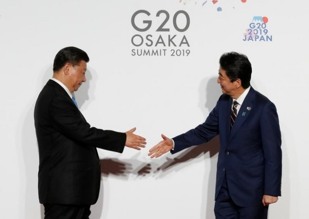 Chinese President Xi Jinping is welcomed by Japanese Prime Minister Shinzo Abe upon his arrival for a welcome and family photo session at G20 leaders summit in Osaka, Japan, June 28, 2019.   REUTERS/Kim Kyung-Hoon/Pool - RC1621D81DA0
