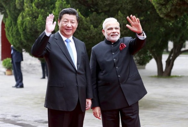 Chinese President Xi Jinping (L) and Indian Prime Minister Narendra Modi wave as they visit Dacien Buddhist Temple in Xian, Shaanxi province, China, May 14, 2015. REUTERS/China Daily CHINA OUT. NO COMMERCIAL OR EDITORIAL SALES IN CHINA - GF10000094720