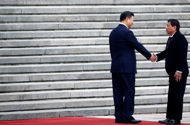 Philippines President Rodrigo Duterte and Chinese President Xi Jinping shake hands as they attend a welcoming ceremony at the Great Hall of the People in Beijing, China, October 20, 2016. REUTERS/Thomas Peter - S1BEUHZJZGAA